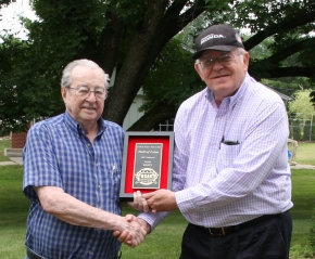 Don White accepts his USAC Hall of Fame plaque from Dick Jordan in a 2013 ceremony in Keokuk, Iowa.