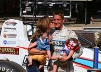 "Justin Grant enjoys the spoils of victory with wife Ashley and their twins after winning Saturday's ""Bettenhausen 100"" at the Illinois State Fairgrounds in Springfield."