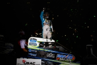 "Justin Grant celebrates his first career USAC National Midget victory Saturday night in the ""Shamrock Classic"" at the Southern Illinois Center in Du Quoin."