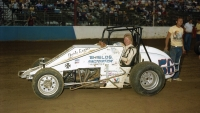 Driver Kelly Kinser poses in the Jerry Shields owned No. 65 before a USAC National Sprint Car feature in 1983, while Shield looks on.